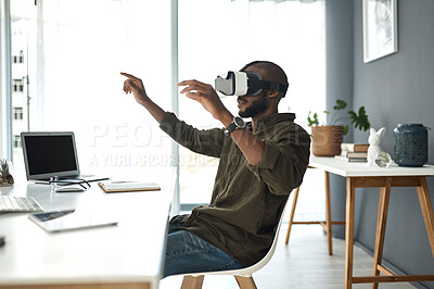 Buy stock photo Shot of a young businessman using a virtual reality headset in a modern office