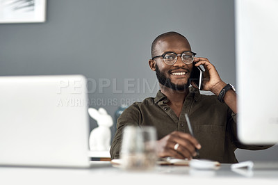 Buy stock photo Shot of a young businessman using a smartphone and computer in a modern office