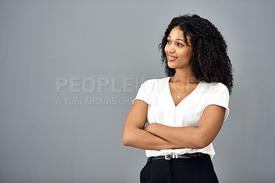 Buy stock photo Studio shot of a confident young businesswoman looking thoughtful against a gray background
