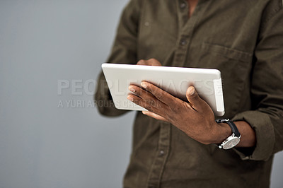 Buy stock photo Studio shot of an unrecognisable businessman using a digital tablet against a gray background