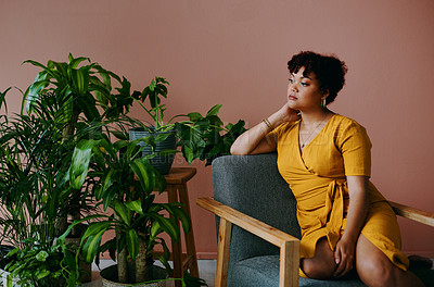 Buy stock photo Shot of a young woman relaxing with plants around her at home