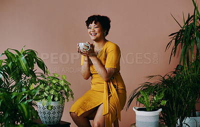 Buy stock photo Shot of a young woman drinking coffee while relaxing with plants around her against a brown background
