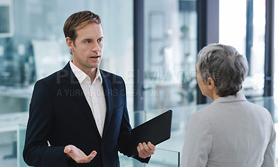 Buy stock photo Shot of a mature businessman talking to a colleague in an office
