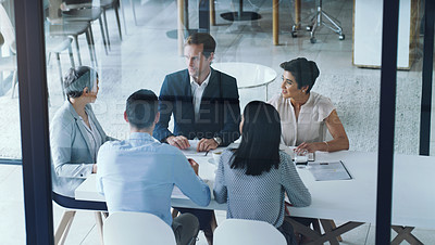 Buy stock photo High angle shot of a group of businesspeople having a meeting in a boardroom