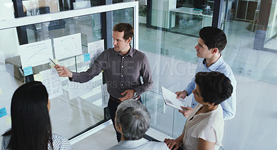 Buy stock photo Shot of a group of businesspeople brainstorming with notes on a glass screen in an office