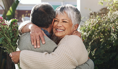 Buy stock photo Shot of a senior man surprising his wife with a bunch of flowers at home