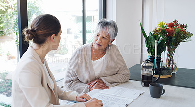 Buy stock photo Shot of a senior woman meeting with a consultant to discuss paperwork at home