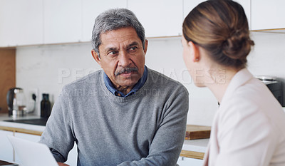Buy stock photo Shot of a senior man using a laptop during a meeting with a consultant at home