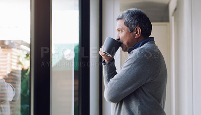 Buy stock photo Shot of a senior man drinking coffee and looking thoughtfully out of a window