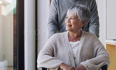 Buy stock photo Shot for a senior woman being being pushed around a nursing home by her husband