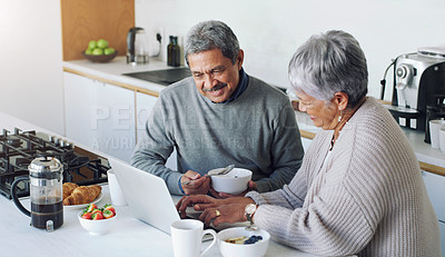 Buy stock photo Shot of a senior couple using a laptop while having breakfast at home