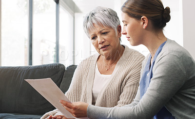 Buy stock photo Shot of a senior woman having a consultation with a doctor at home
