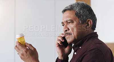 Buy stock photo Shot of a senior man reading the label on a medicine container and talking on a cellphone