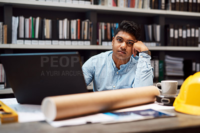 Buy stock photo Portrait of a young architect looking bored while working at his desk in a modern office