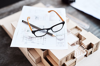 Buy stock photo Shot of glasses, a pencil, blueprint and building model on a desk in an office