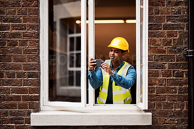 Buy stock photo Shot of a young engineer taking pictures while looking out the window of a construction site