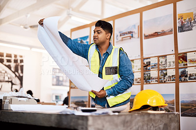 Buy stock photo Shot of a young architect looking at a blueprint in his office