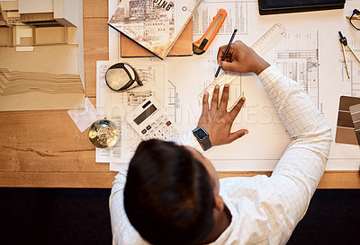 Buy stock photo High angle shot of an architect using a ruler to draw a building plan