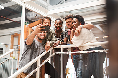 Buy stock photo Shot of a group of young creatives taking selfies together in an office