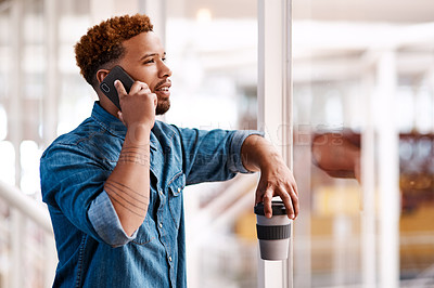 Buy stock photo Cropped shot of a handsome young male designer making a phonecall while standing at at a window in his office