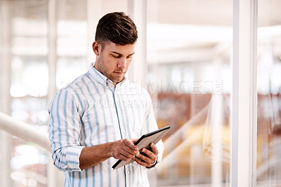 Buy stock photo Cropped shot of a handsome young male designer using his tablet while standing in the office