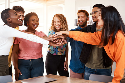 Buy stock photo Cropped shot of a group of young designers standing with their hands in a huddle in the office
