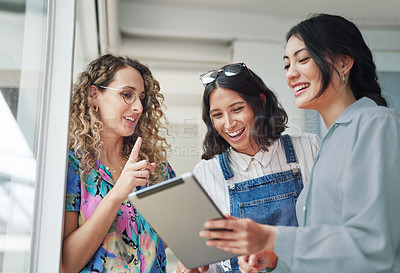 Buy stock photo Shot of a group of businesswomen using a digital tablet together in an office