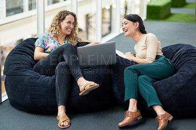 Buy stock photo Shot of two businesswomen using a laptop together while sitting on beanbags in an office