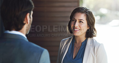 Buy stock photo Shot of a young businesswoman having a discussion with a colleague outside an office