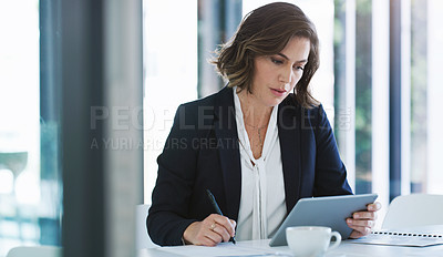 Buy stock photo Shot of a young businesswoman using a digital tablet while going through paperwork in an office