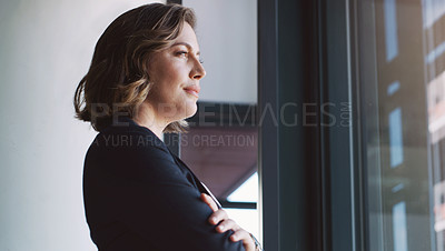 Buy stock photo Shot of a young businesswoman looking thoughtfully out a window in an office