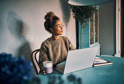 Buy stock photo Shot of a young woman looking thoughtful while using a laptop at home