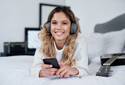 Buy stock photo Shot of a young woman wearing headphones and holding her cellphone while lying on her bed