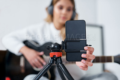 Buy stock photo Shot of a young woman using her cellphone to record herself while playing the guitar at home