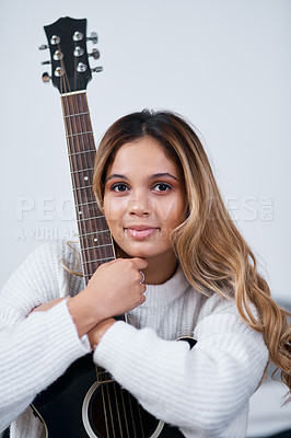 Buy stock photo Cropped shot of a young woman sitting at home with her guitar