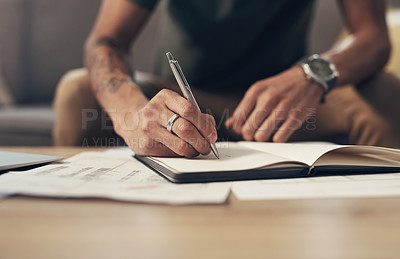 Buy stock photo Cropped shot of an unrecognisable man going over paperwork at home