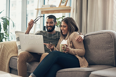 Buy stock photo Shot of a young couple using a laptop and credit card on the sofa at home