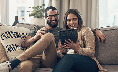 Buy stock photo Shot of a young couple using a digital tablet and credit card on the sofa at home
