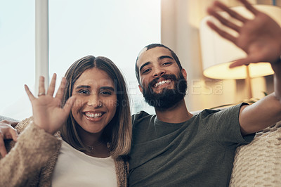 Buy stock photo Portrait of a happy young couple waving during a video call on the sofa at home