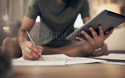 Buy stock photo Cropped shot of a man using a digital tablet while going through paperwork at home