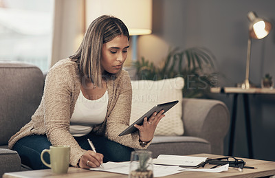 Buy stock photo Shot of a young woman using a digital tablet while going through paperwork at home