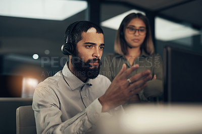 Buy stock photo Shot of a call centre agent working in an office alongside a colleague at night