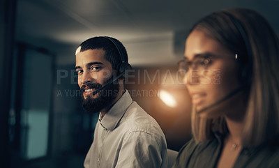 Buy stock photo Portrait of a call centre agent working in an office alongside a colleague at night