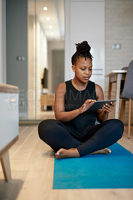 Buy stock photo Shot of a young woman using a digital tablet while doing yoga at home