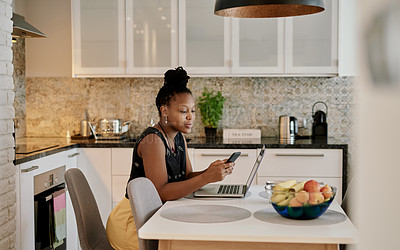 Buy stock photo Shot of a young woman using her cellphone while sitting at home with her laptop