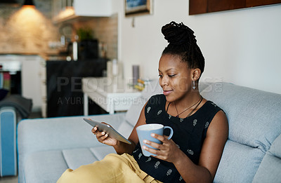 Buy stock photo Shot of a young woman using a digital tablet while sitting on the couch at home
