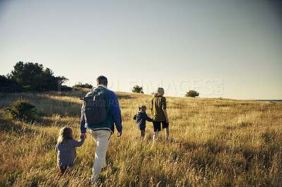 Buy stock photo Rearview shot of a young couple out on an adventure together with their two kids