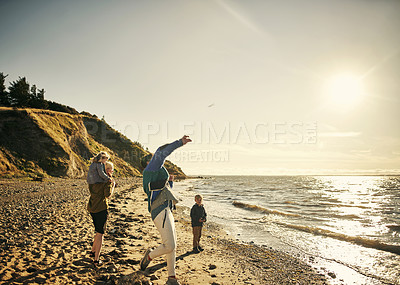 Buy stock photo Shot of a young family of four out on the beach together