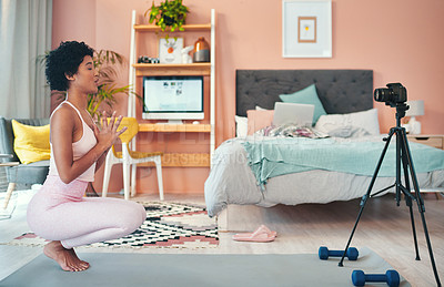Buy stock photo Shot of a young woman recording herself while exercising at home