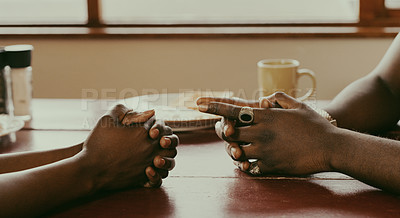 Buy stock photo Cropped shot of an unrecognizable couple sitting together at a table